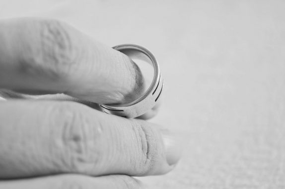 Removing wedding ring in conscious uncoupling move - hand and ring being separated