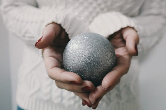 Silver bauble in hands of woman wearing winter jumper, representing Christmas and sensory stimulation - a worry for children with Autism