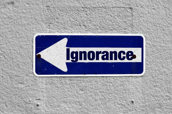 Facing ignorant GP described using Ignorance sign on white wall