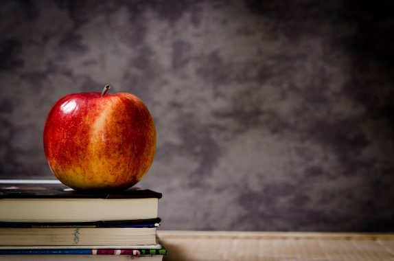 Back to school scene with desk, apple, blackboard and books. Typical school picture.