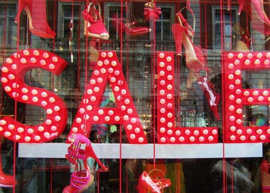 Sale sign in big red letters with lighting, surrounded by red shoes in a range of styles