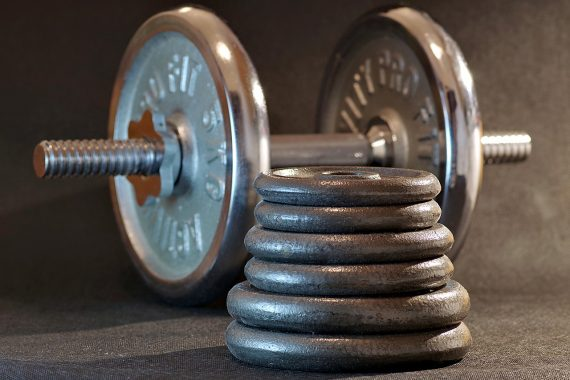 Weights on a bar at the gym and in a pile in the foreground