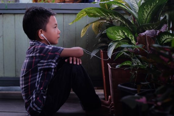 Child sitting on the floor with headphones on to represent autism and spread autism awareness