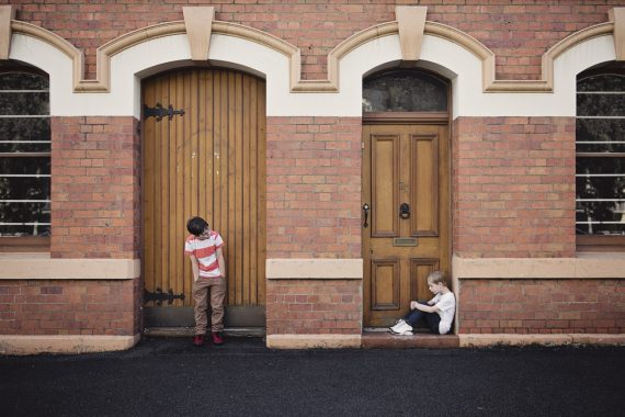 Children in doorways: one standing in front of ornate wooden door, the other sitting in front of smaller door, showing child poverty comparisons