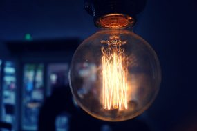 Lightbulb in darkened room with glowing filaments to symbolise brain and thinking processes
