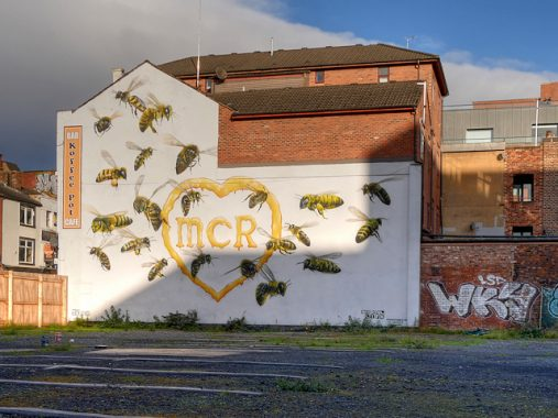 MCR heart with bees symbol of Manchester painted as mural on wall after Manchester terror attacks