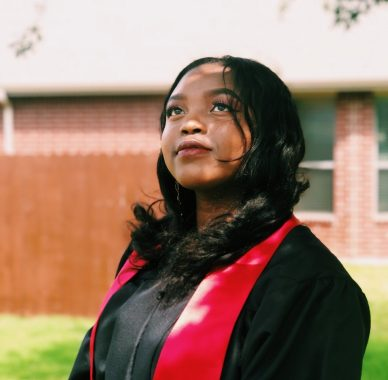 University graduate looking upwards in black graduating gown with red trim, standing in front of building and grass