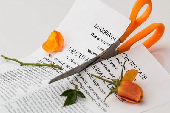 Marriage contract cut up with orange scissors and broken flower laid on top, symbolising separation and divorce